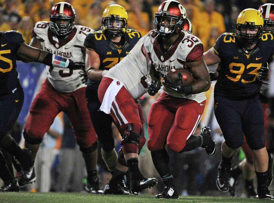 Oklahoma's Samaje Perine (32) runs past the West Virginia defense during the fourth quarter of an NCAA college football game in Morgantown, W.Va., on Sept. 20, 2014. Photo: Tyler Evert /Associated Press / FR170609