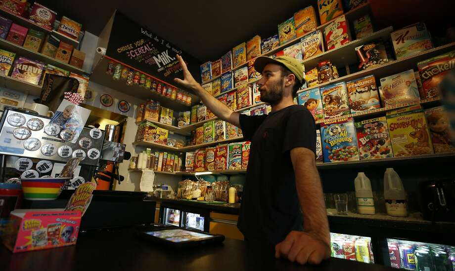 An employee at the Cereal Killer Cafe in Brick Lane, London, helps point out to a customer the range of cereals available from American favorites to European gluten free organics. Photo: Alastair Grant, Associated Press
