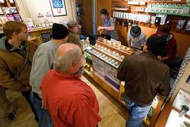 Employees of Amazon Organics, a pot dispensary in Eugene, Ore., help customers purchase recreational marijuana on Thursday, Oct. 1, 2015. Oregon marijuana shops began selling marijuana Thursday for the first time to recreational users who are at least 21 years old, marking a big day for the budding pot industry.