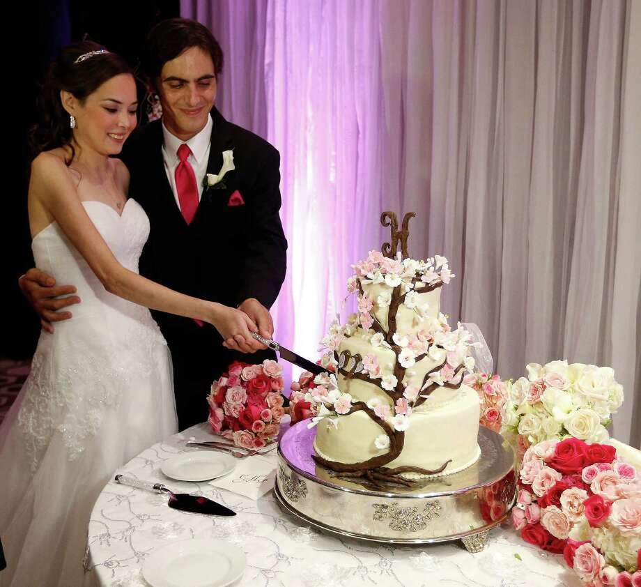 """Catherine and Peter cut their cake during  the reception for their """"Wish Upon a Wedding"""" wedding at Hotel Derek on Tuesday, Sept. 8, 2015. Catherine and Peter are from McAllen.  Catherine suffers from cystic fibrosis and is currently awaiting a double-lung transplant that could extend her life. Wish Upon a Wedding is a non-profit that utilizes high end wedding planners and photographers to give their talents to make dreams come true for couples facing life threatening ordeals to be able to find hope. ( Karen Warren / Houston Chronicle ) Photo: Karen Warren, Staff / © 2015 Houston Chronicle"""