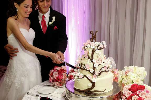 """Catherine and Peter cut their cake during  the reception for their """"Wish Upon a Wedding"""" wedding at Hotel Derek on Tuesday, Sept. 8, 2015. Catherine and Peter are from McAllen.  Catherine suffers from cystic fibrosis and is currently awaiting a double-lung transplant that could extend her life. Wish Upon a Wedding is a non-profit that utilizes high end wedding planners and photographers to give their talents to make dreams come true for couples facing life threatening ordeals to be able to find hope. ( Karen Warren / Houston Chronicle )"""
