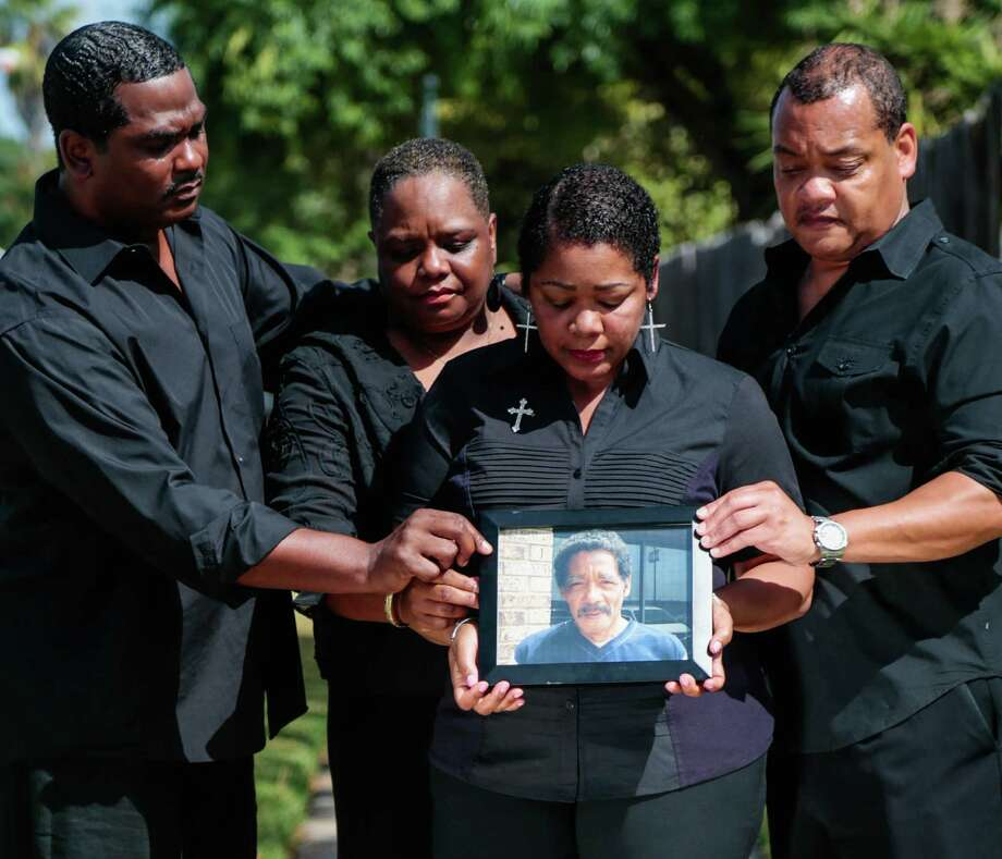 (l-r) Jason Hicks, Marie Hicks-Fields, Evangeline Campbell, and Norman Hicks Jr. all hold on to a photo Norman Hicks Sr. They have filed a wrongful death lawsuit against Harris County. Photo: Billy Smith II, Chronicle / Houston Chronicle