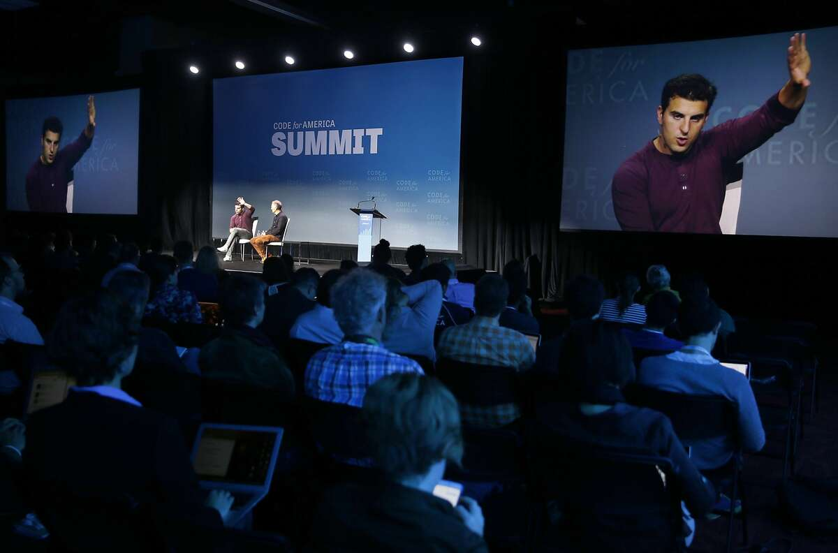 Airbnb CEO and co-founder Brian Chesky appears on the big screen during his chat with technology books publisher Tim O'Reilly at the Code for America Summit conference in Oakland, Calif. on Thursday, Oct. 1, 2015.