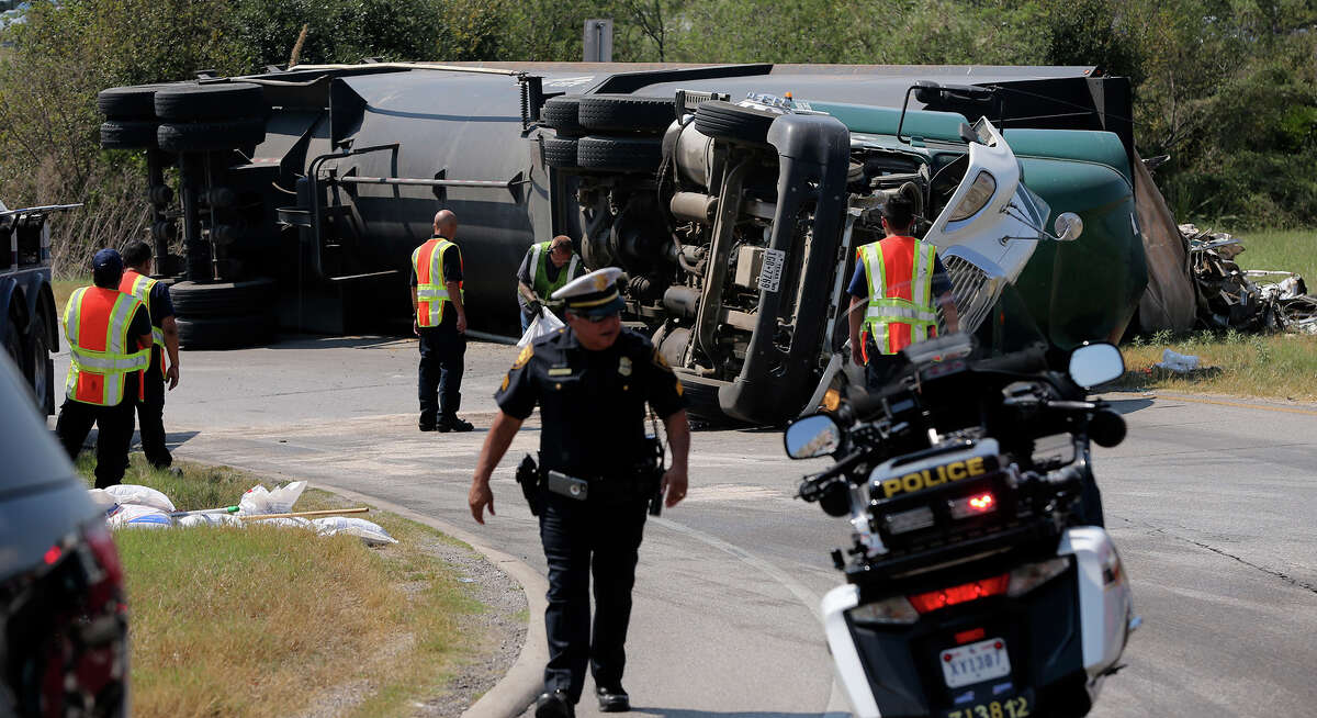 San Antonio police, fire and wrecker personnel work Thursday October 1, 2015 at the scene of an 18-wheeler tractor trailer crash that took place early in the afternoon on the ramp going from south loop 410 east bound to I-35 southbound. An officer at the scene said speed may have been a factor in the overturned vehicle's crash and there were no serious injuries. The overturned rig spilled its load of scrap metal that included kitchen sinks.