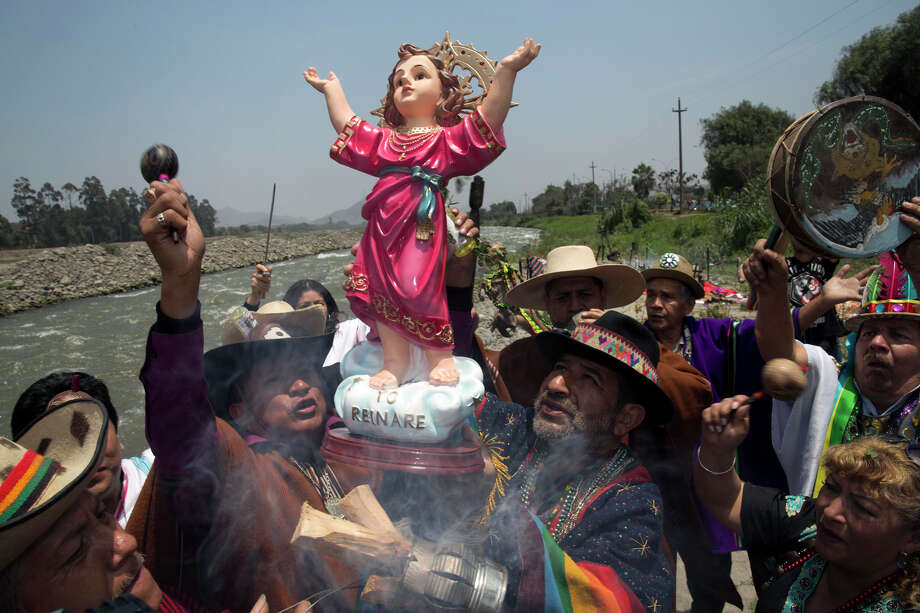"""Shamans hold up a statue of baby Jesus, or """"El Nino"""" in Spanish, as they play drums and maracas during a ritual asking for protection from the natural phenomenon known as El Nino, on the outskirts of Lima, Peru, Thursday, Oct. 1, 2015. Photo: Martin Mejia, AP / AP"""