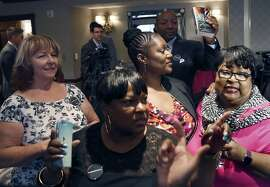 Linda Carlson (left), Dininne Neal (front), Tira McDonald, (middle), and Deborah Neal (right) are some of eleven women who announce in San Francisco, Calif., on Thursday, October 1, 2015, a racial discrimination suit against the Napa Valley Wine Train for evicting them from the train for being too loud.  Civil rights attorney Waukeen McCoy seen behind with book.