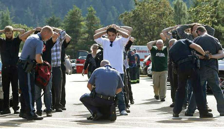 Police search students outside Umpqua Community College in Roseburg, Ore., after a deadly attack on the college campus. Law enforcement officials  say the 20-year-old man who went on the shooting rampage was killed in a gunfight  with police officers. Photo: Mike Sullivan, Associated Press