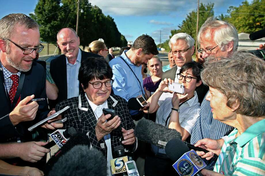 Death penalty opponent Sister Helen Prejean, center, tries to put death row inmate Richard Glossip on speaker phone outside the Oklahoma State Penitentiary, following a stay in his scheduled execution, in McAlester, Okla., Wednesday, Sept. 30, 2015. (AP Photo/Sue Ogrocki) Photo: Sue Ogrocki, STF / AP