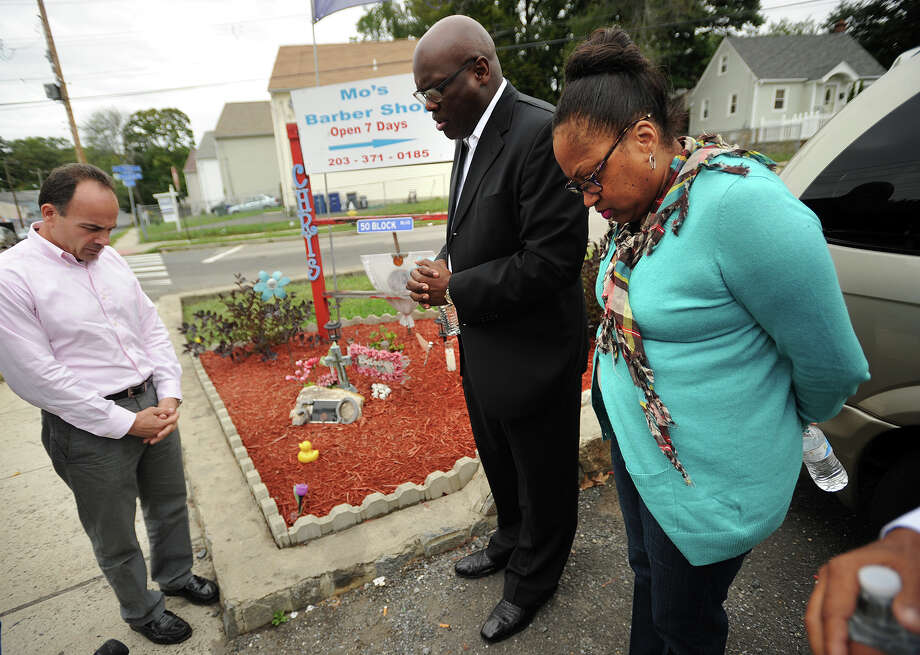 From left; Bridgeport mayoral candidate Joe Ganim, State Rep D-126 Rev. Charlie Stallworth, and Jacqueline Pettway bow their heads in a prayer by a memorial for Pettway's son, LaChristopher Pettway, on Reservoir Avenue in Bridgeport, Conn. on Thursday, October 1, 2015. A young man was shot in the vicinity on Tuesday night. LaChristopher Pettway was shot and killed at the site on September 10, 2013. Photo: Brian A. Pounds, Hearst Connecticut Media / Connecticut Post