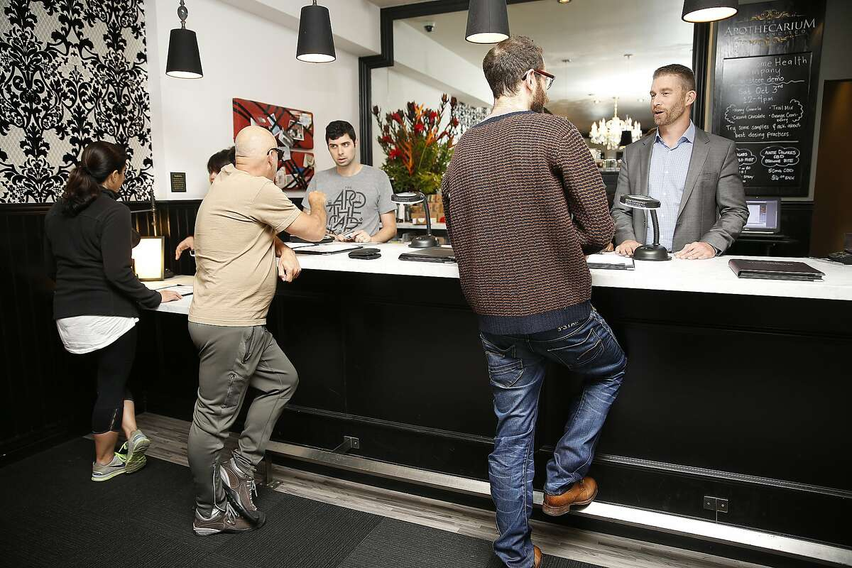Co-founder and executive director Ryan Hudson (far right) talks with customer Beau Freshour (brown sweater) at The Apothecarium, a medical marijuana dispensary in San Francisco, Calif., on Thursday, October 1, 2015. Governor Jerry Brown is expected to sign bills to regulate the medicinal weed industry today.