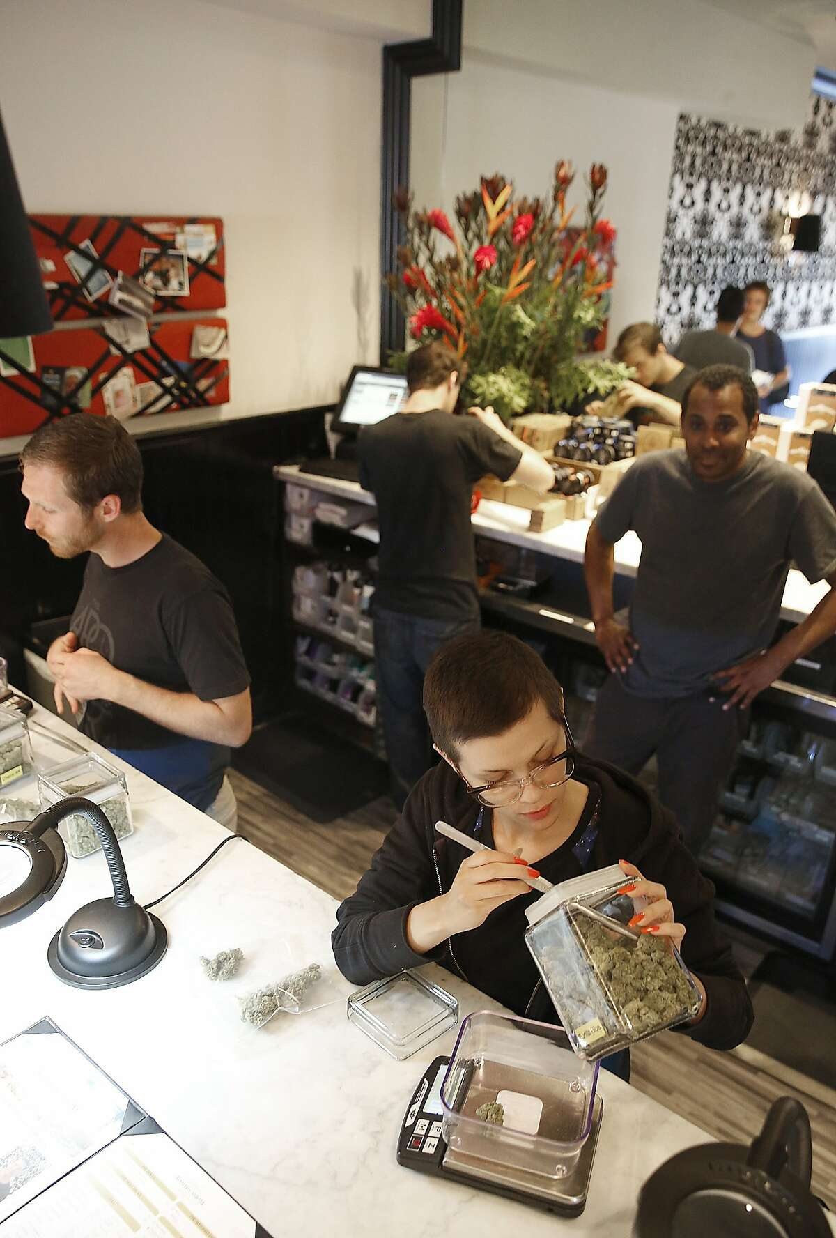 Patient consultants Josh Cremer (left) and Camille Wood (front) help customers at The Apothecarium, a medical marijuana dispensary in San Francisco, Calif., on Thursday, October 1, 2015. Governor Jerry Brown is expected to sign bills to regulate the medicinal weed industry today.