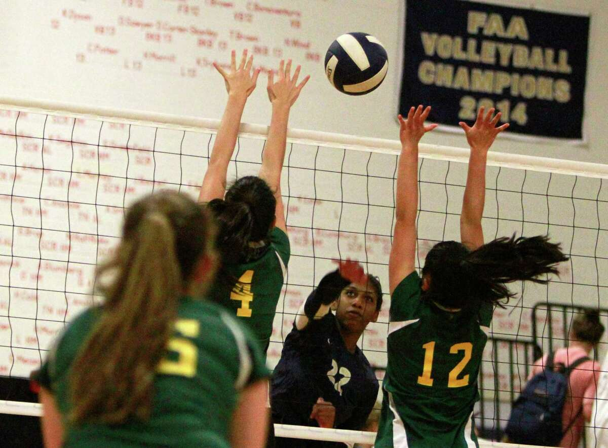 King's Kayonne Markes (22) slaps the ball past Greenwich Academys' Natalie Threadgill (4) and Jessica Liu (12) during a varsity girls volleyball match in Stamford on Thursday, Oct. 1, 2015.