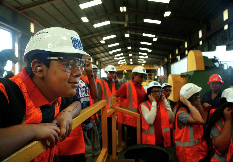 David Sanchez, 13, peers over a railing during a tour of the Storage & Processors steel processing plant. Photo: Mark Mulligan, Staff / © 2015 Houston Chronicle