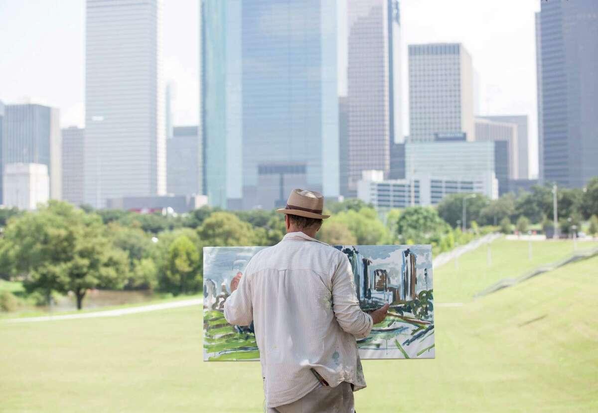 Arthur Deatly paints the city skyline in the Buffalo Bayou area.