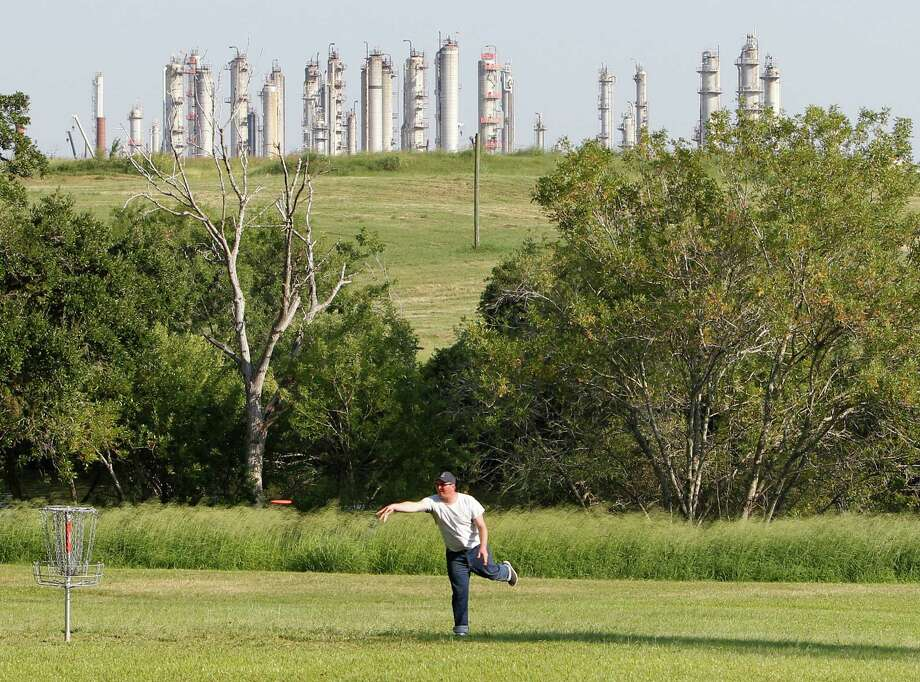 """Pasadena, Tx resident Lee Cantin throws his frisbee at the second hole in Milby Park,  Thursday, Oct. 1, 2015, in Houston.   The Obama Administration on Thursday unveiled a controversial and long-delayed environmental regulation that will curtail emissions of lung-irritating ozone, putting smoggy cities such as Houston even further behind in efforts to comply with the federal limit. U.S. Environmental Protection Agency officials set the new standard at 70 parts per billion of ozone in the air, dismaying both public health officials seeking greater smog reductions and industry leaders, who wanted the government to leave the standard at 75 parts per billion. The EPA said tightening of the ozone standard is supported by a growing body of scientific evidence linking the pollutant to harmful health effects, including asthma, heart disease and premature death. The new standard will """"substantially increase public health protection,"""" said EPA Administrator Gina McCarthy. """"There is absolutely no question about that.""""    ( Steve Gonzales / Houston Chronicle ) Photo: Steve Gonzales, Staff / © 2015 Houston Chronicle"""