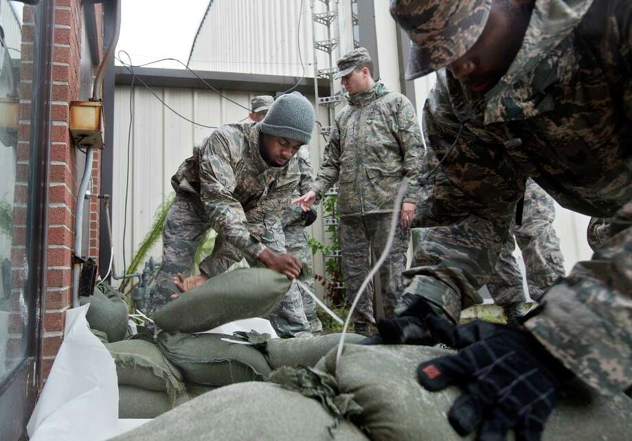 Airmen and volunteers place sandbags outside of a building at Langley AFB as heavy rain falls in Hampton, Va. The base will be closed to all non-mission-essential personnel beginning this morning. Photo: Kaitlin McKeown /(Newport News, Va.) Daily Press / The Daily Press