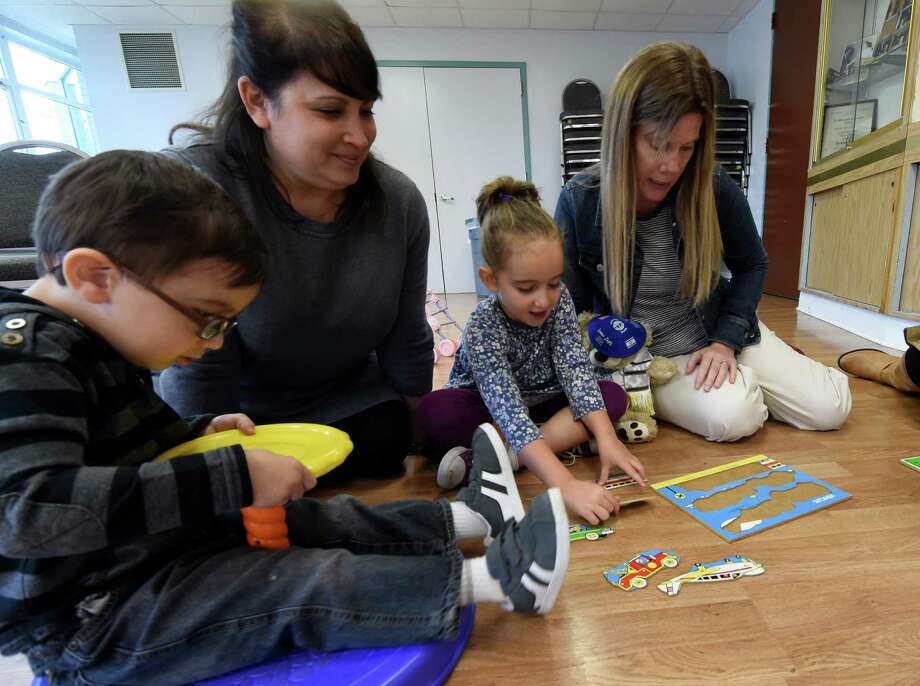 Parents and children gather at the PJ Library which is open to all for kids activities at the Albany Jewish Community Center Thursday morning Oct. 1, 2015 in Albany, N.Y.  Attending this morning from left;  Nicholas Eisenberg, 3, with his mom Jamie Eisenberg as well as Poppy Eisenberg,4, and instructor Amy Drucker.        (Skip Dickstein/Times Union) Photo: SKIP DICKSTEIN / 00033526A