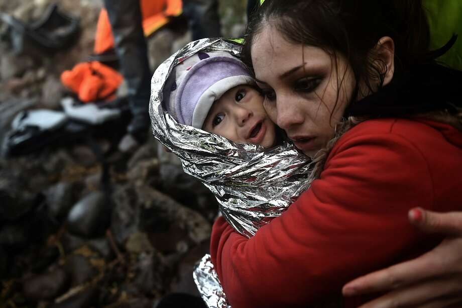 A woman hugs a baby wrapped in an emergency blanket as refugees and migrants arrive on the Greek island of Lesbos after crossing the Aegean sea from Turkey on October 1, 2015. The UN refugee agency UNHCR said it expects 700,000 migrants and refugees to reach Europe via the Mediterranean this year and projected at least the same amount again in 2016.  Photo: Aris Messinis, AFP / Getty Images