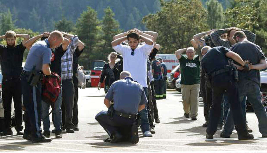 Police search students outside Umpqua Community College in Roseburg, Ore.,  Thursday following a deadly shooting at the college. Photo: Mike Sullivan, MBO / Roseburg News-Review