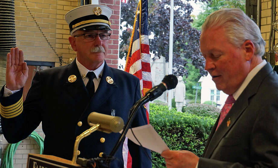 Denis McCarthy is sworn in as the town's new fire chief Thursday by First Selectman Mike Tetreau. Photo: Genevieve Reilly / Fairfield Citizen / Fairfield Citizen