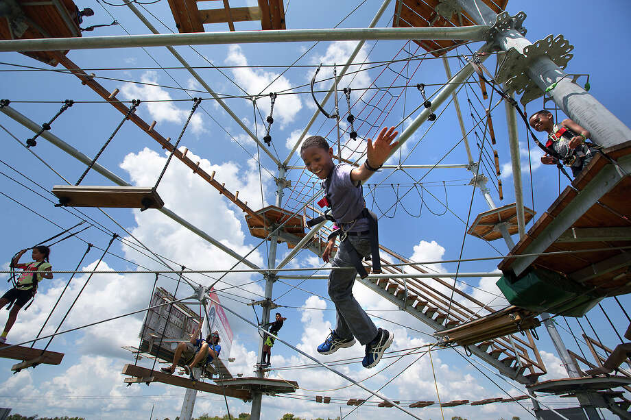 Daniel Russell, 10, dangles from the new Aerial Adventure Ropes Course at Wake Nation Houston. Photo: Cody Duty, Staff / © 2015 Houston Chronicle