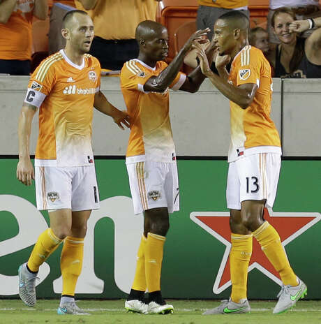 Houston Dynamo's Brad Davis, left, and teammates DaMarcus Beasley, and Ricardo Clark, right, celebrate goal by Will Bruin during the second half of MLS game at BBVA Compass Stadium Wednesday, Sept. 23, 2015, in Houston. ( Melissa Phillip  /  Houston Chronicle ) Photo: Melissa Phillip, Staff / © 2015 Houston Chronicle