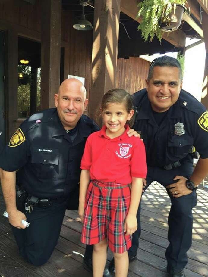 A young girl showed her support for the San Antonio Police Department last week by giving a free candy bar to officers Arturo Hernandez and Scott Boehm. Photo: San Antonio Police Department