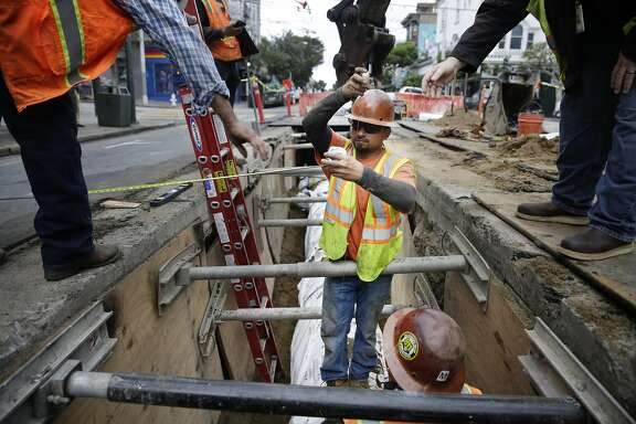 Cesar Robles (center), San Francisco Water Department laborer, uses a weight to measure distance and alignment of the replacement water pipes as they work on the pipeline replacement project along Haight Street at Ashbury Street on Thursday, October 1, 2015 in San Francisco, Calif.