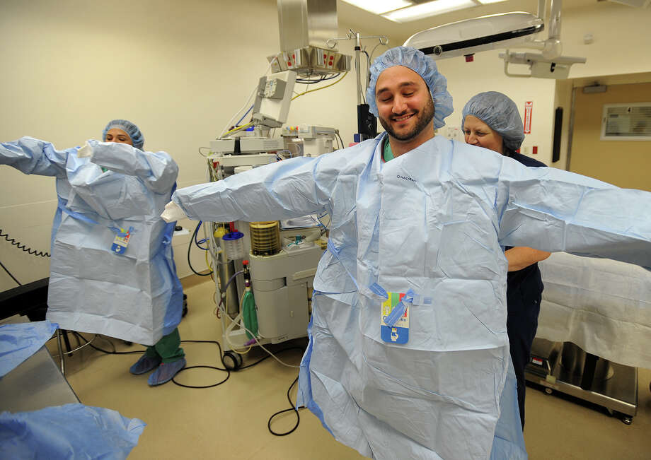 Quinnipiac University medical students Danielle Bottalico, left, of Danbury, and Howard Furlong, of Berlin, put on sterile surgical gowns with the aid of Clinical Nurse Educator Kim Adler in an operating room at St. Vincent's Hospital in Bridgeport, Conn. on Thursday, October 1, 2015. Bottalico and Furlong are members of Quinnipiac Medical School's  inaugural class. Photo: Brian A. Pounds / Hearst Connecticut Media / Connecticut Post