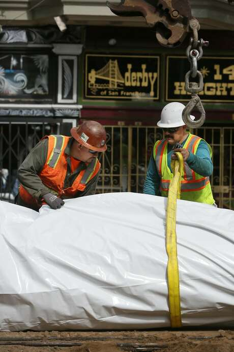 Martin Santos (left) and Arturo Morones secure a wrap to prevent corrosion around a replacement pipeline along Haight Street in San Francisco. Photo: Lea Suzuki, The Chronicle
