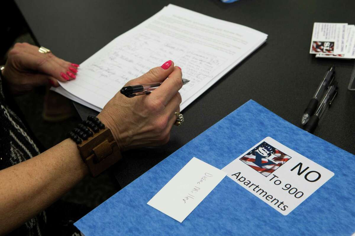 Ann Magoon, center, a neighbor of Sugar Land listens to the referendum petition to rescind Ordinance 2014 before signing, Monday, Sept. 21, 2015, in Sugar Land. ( Marie D. De Jesus / Houston Chronicle )