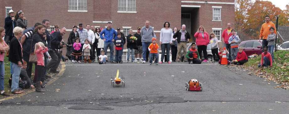 Spectators enjoy the competition between two pumpkin racers at the Newtown Lions' Great Pumpkin Race. This year's event will be Saturday, Oct. 17. Photo: Contributed Photo