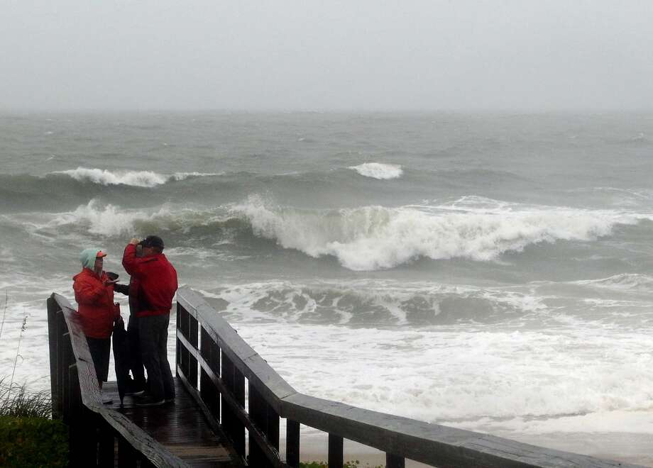 People watch the waves in a rainstorm at Atlantic Ocean at Carolina Beach, N. C., Friday, Oct. 2, 2015. Millions along the East Coast breathed a little easier Friday after forecasters said Hurricane Joaquin would probably veer out to sea instead of joining up with a drenching rainstorm that is bringing severe flooding to parts of the Atlantic Seaboard. (AP Photo/Harry Hamburg) Photo: Harry Hamburg, Associated Press