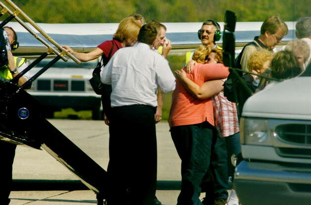Survivors of the Ethan Allen boat tragedy Margie Kidon gets a hug from an unidentified woman as her husband Bob Kidon wipes his eyes as they get off the corporate jet they flew in from Queensbury, N.Y., to Romulus, Mich., three days after the boat capsized on Lake George in October 2005. (Michael P. Farrell/Times Union archive) Photo: MICHAEL P. FARRELL / ALBANY TIMES UNION