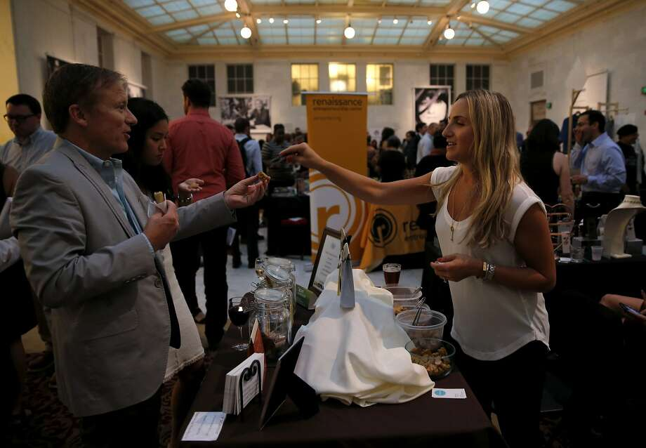 Marlo Gertz, owner of Marlo's Bakeshop, (right) gives a sample to Pierce Buxton at an event sponsored by Kiva at San Francisco City Hall in San Francisco, California, on Thursday, Oct. 1, 2015. Photo: Connor Radnovich, The Chronicle