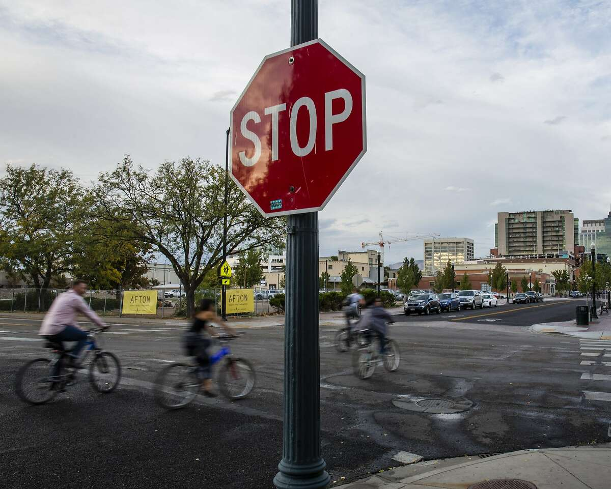 Bicyclists rolls through a stop sign at 8th and River Streets on Thursday, October 1, 2015, in Boise, Idaho.
