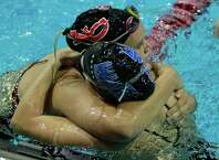 New Canaan's Meghan Egan, left, and Darien's Phoebe Slaughter hug each other after battling it out in the 200 individual medley during their swim meet Thursday in New Canaan.