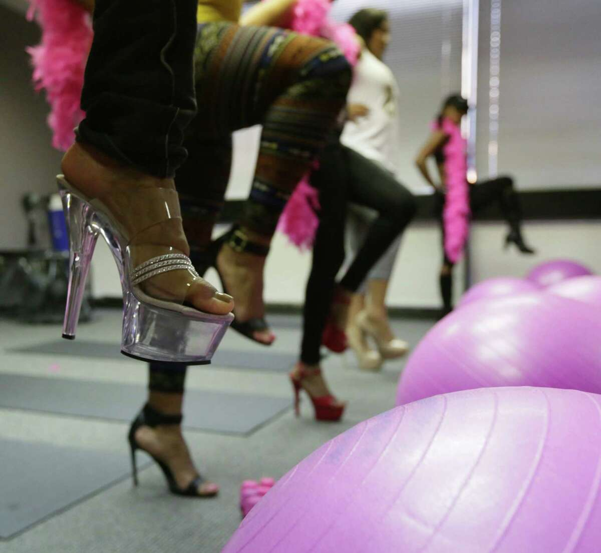 Women exercise in stiletto heels during the Naked Fin Piletto class, Saturday, Sept. 26, 2015, in Houston.