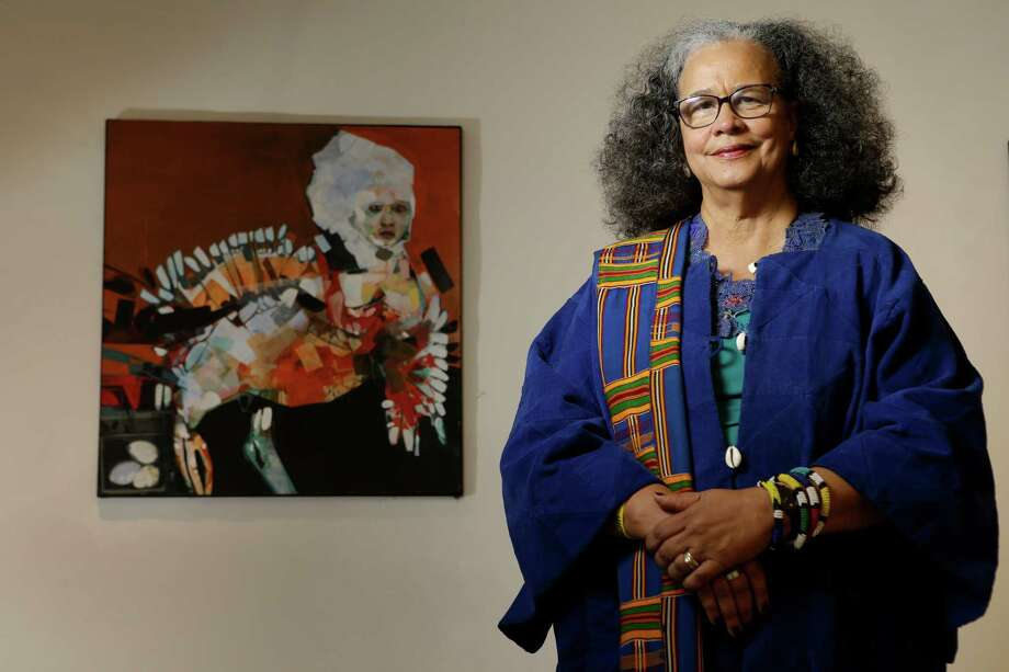 "Michelle Barnes, co-founder and executive director of the Community Artists' Collective, poses in front of the work by artist Ron Smith titled ""Wildlife"" while wearing one of her favorite garments.  Photo: Melissa Phillip, Staff / © 2015 Houston Chronicle"