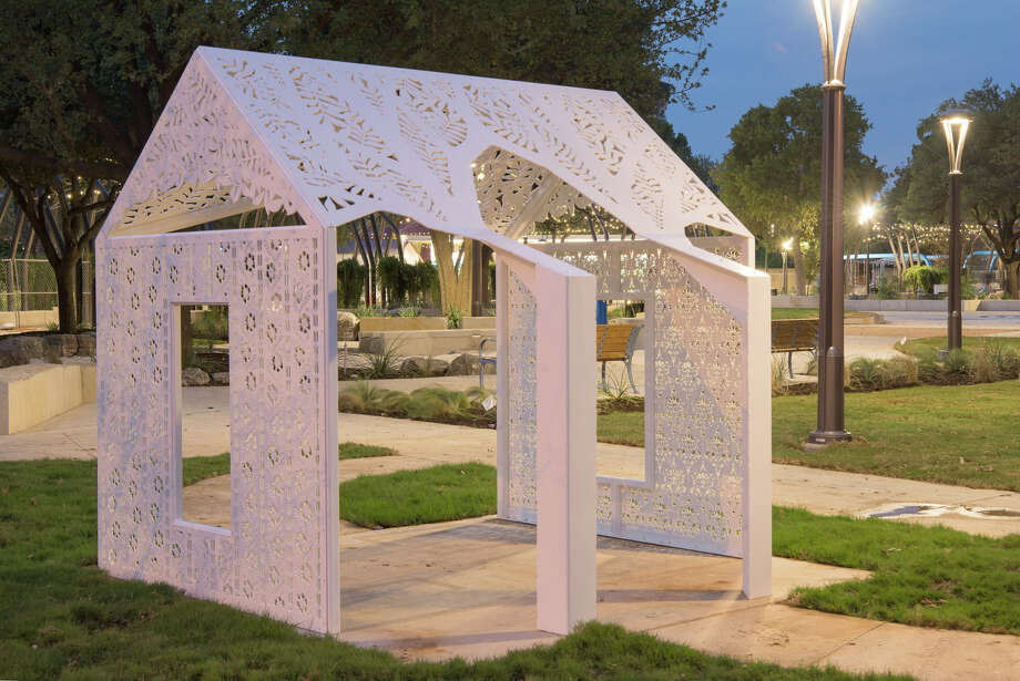 """PLAYhouse"" by Karen Mahaffy is a miniature saltbox-style metal structure with perforated walls that cast shadows in vintage wall paper patterns. It is one of the works in ""PLAY,"" a series of kid-friendly interactive artworks in Yanaguana Garden."" Photo: Courtesy Stuart Allen Art Services"