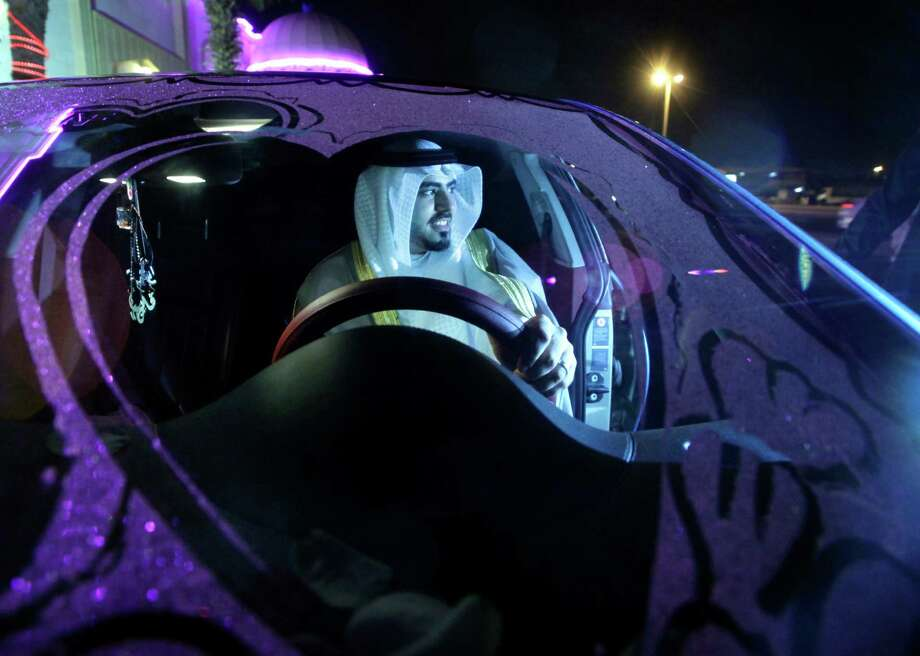 Saudi groom Hisham Saleh Edris drives his decorated car recently in Jiddah, Saudi Arabia. A drop in oil revenue is forcing Saudi Arabia to weigh its first cuts to welfare and investment in years. Currently, thanks to subsidies, the price of a gallon of gasoline is 45 cents. Photo: Amr Nabil, STF / AP