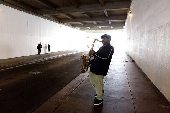 Jerry Woo, 54, plays his saxophone on Minna Street in downtown San Francisco, Calif. on Monday, September 28, 2015. Woo said he is addicted to the acoustics in the tunnel. (Photo by Tim Hussin)