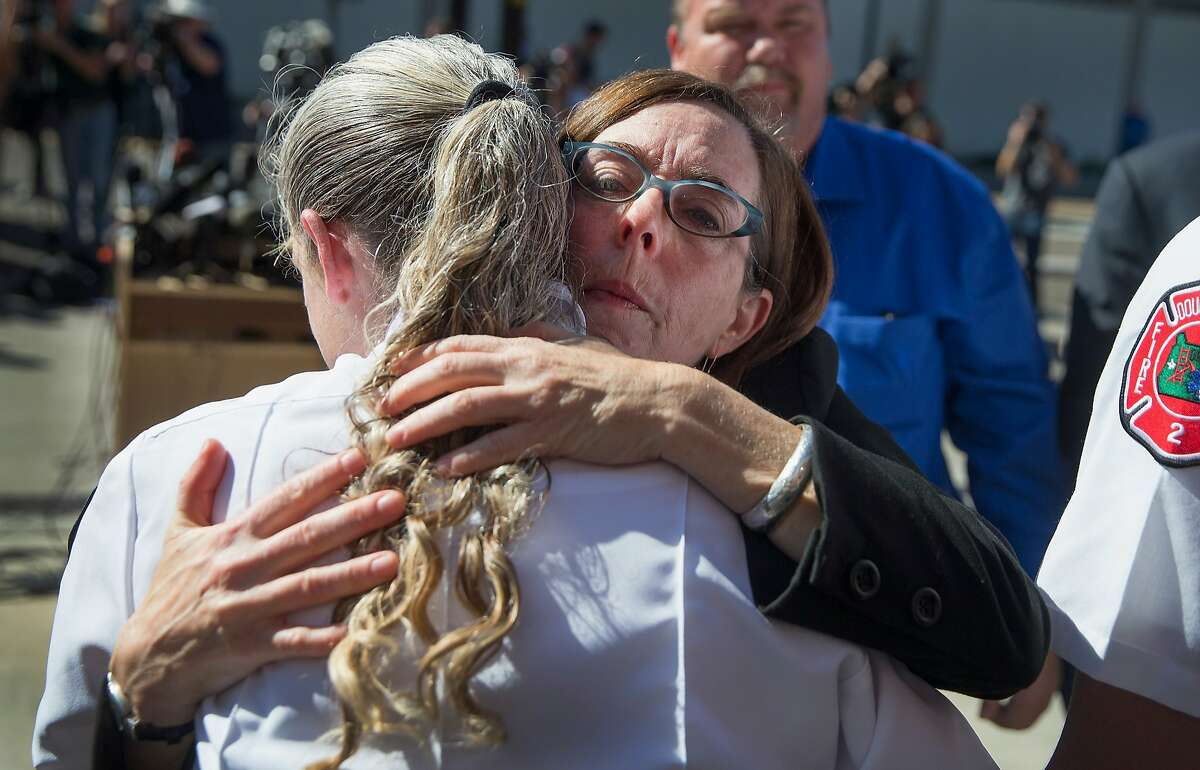 Oregon governor Kate Brown (R) hugs Battalion Chief Teresa Mutschleras she was thanking first responders for their efforts yesterday at Umpqua Community College on October 2, 2015 in Roseburg, Oregon. Yesterday 26-year-old Chris Harper Mercer went on a shooting rampage at the campus, killing 9 people and wounding another seven before he was killed.