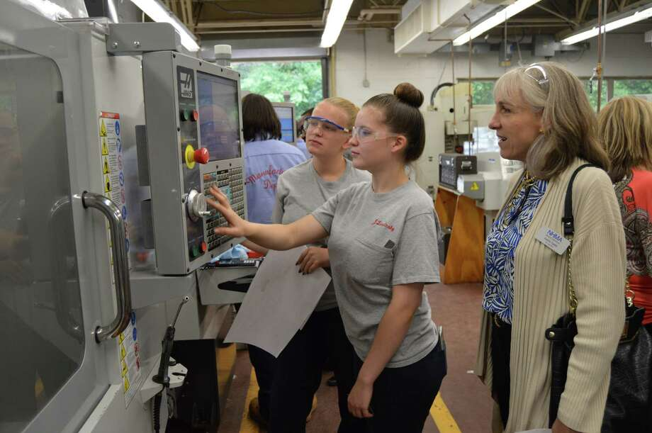Liz Petroski, of Derby, and Jessica Liscinsky, of West Haven, demonstrate how they program a CNC drill to Kathy Saint, president of Schewerdtle Stamp, at Platt Technical School in Milford on Thursday. Photo: Contributed Photo
