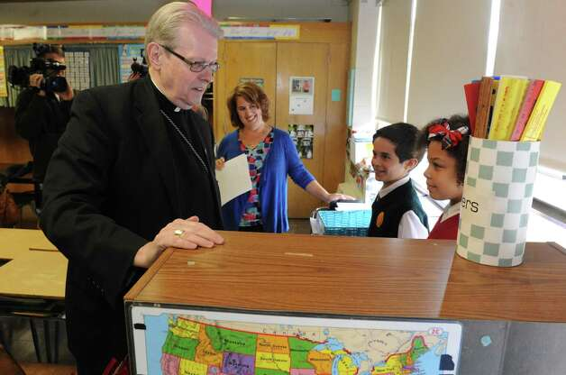 Bishop Edward B. Scharfenberger, left, meets St. Madeleine Sophie students Giada Leigh, right, and Josh Hosey prior to announcing a major shift in the way Common Core-New York State Assessments are implemented at Catholic elementary and middle schools at St. Madeleine Sophie School on Friday Oct. 2, 2015 in Schenectady , N.Y.  (Michael P. Farrell/Times Union) Photo: Michael P. Farrell / 10033609A