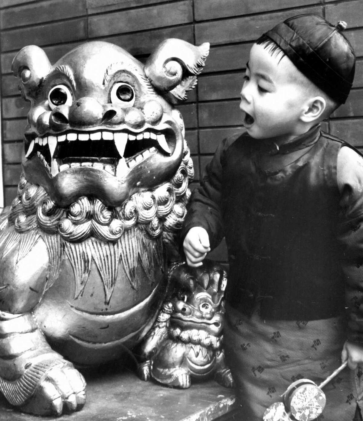 A child standing next to a lion in Chinatown is ready to celebrate the Chinese New Year in 1975. The Chinese won the right to use fireworks in the parade as part of their religion in 1908.