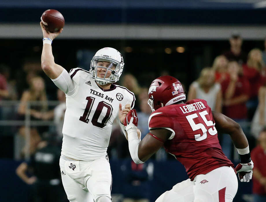 Texas A&M quarterback Kyle Allen passes under pressure from Arkansas defensive lineman Jeremiah Ledbetter during the second half on Saturday, Sept. 26, 2015, in Arlington. Allen completed 21 of 28 passes for 358 yards with two touchdowns in the 28-21 Texas A&M overtime win. Photo: Tony Gutierrez /Associated Press / AP