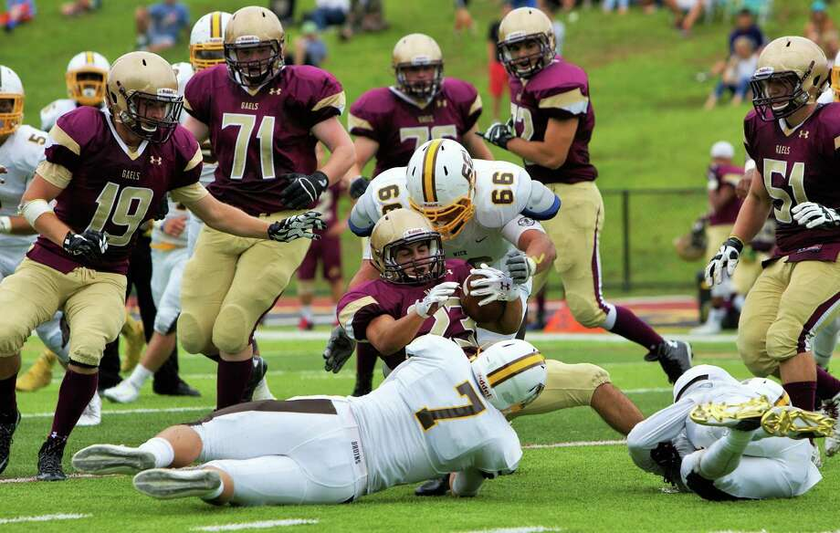 Brunswick's Patrick Adamo (66) and John Fox (7) tackles an Iona Prep runner. Brunswick defeated Iona Prep 26-18 in New Rochelle, NY on Sept. 12, 2015. Photo: Matthew Brown / For Hearst Connecticut Media / Connecticut Post Freelance