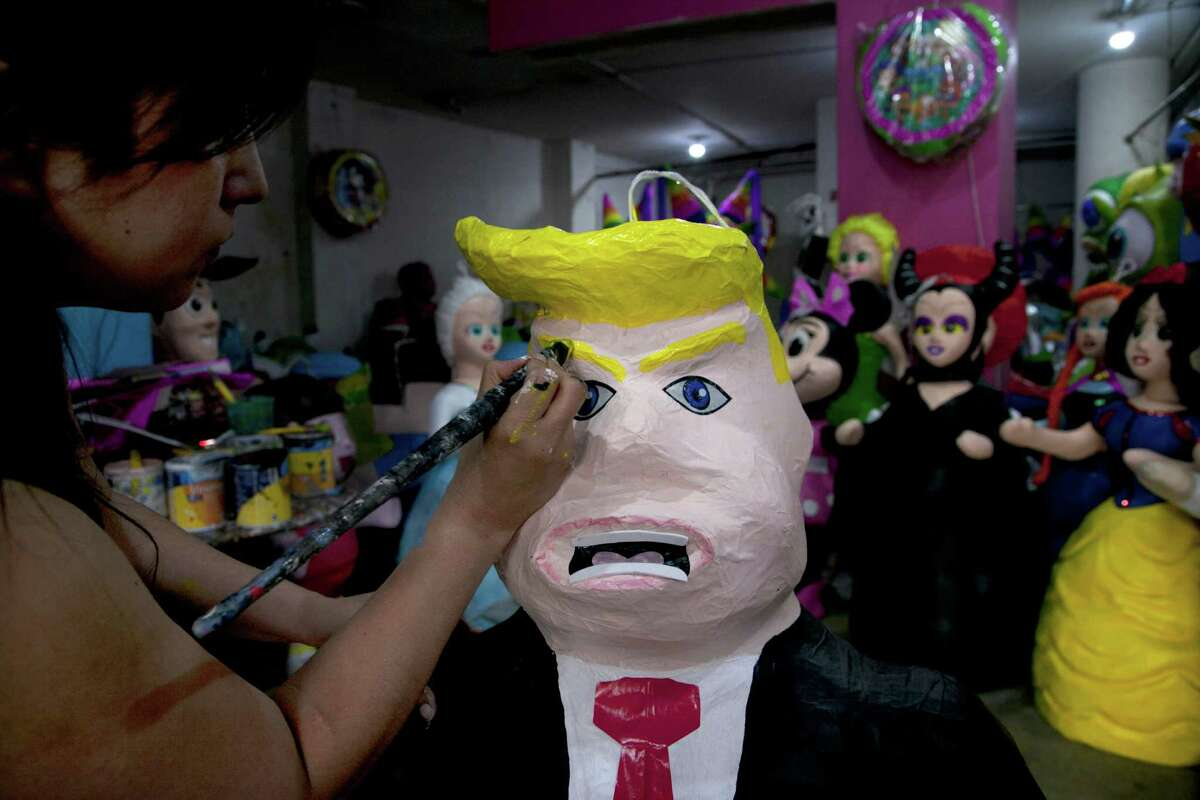 """Alicia Lopez Fernandez paints a pinata depicting Donald Trump at her family's store """"Pié±atas Mena Banbolinos"""" in Mexico City. The pié±ata was a special order made after Trump's comments that some Mexican immigrants to the U.S. bring drugs and crime, and some are rapists. (AP Photo/Marco Ugarte, File)"""