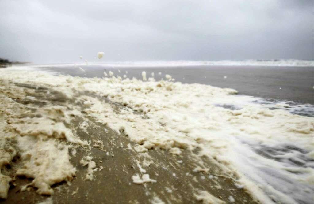 sea foam is blown swiftly along the beach as waves crash along the shore in sea